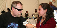 Eric Bloom (lead vocalist for classic rock mega-band Blue Oyster Cult) speaking with WRHU student air talent Jill backstage at a concert at Hofstra.