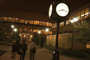 Students walking by Hofstra clock at night