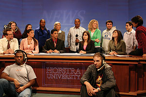 Good Day New York reporter Mike Woods (center, holding microphone) broadcasts live from the Dempster Hall News & Views set to cover a 'newscast in training.'