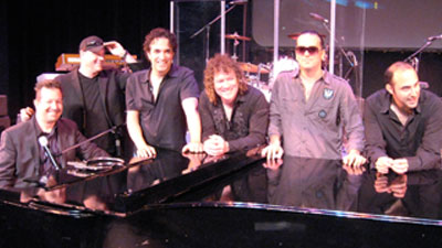 The Movin' Out Band (L to r) Wade Preston, Chuck Burgi, Dennis DelGaudio, Greg Smith, John Scarpulla and Carmine Giglio. Photo by Jen Brunges Mrakovcic.