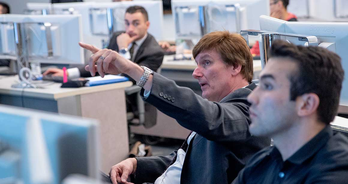 Professor sitting in Trading Room with students